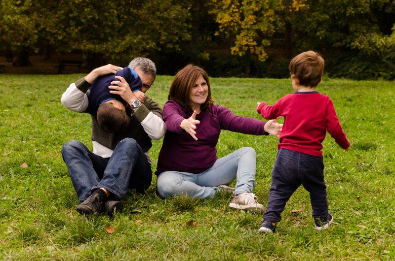 Papá y mamá están sentados juntos sobre el césped. Uno de los niños ha saltado por encima del padre y éste lo tiene cogido boca abajo haciéndole cosquillas. El otro niño está corriendo mientras mamá embarazada le abre los brazos para que corra hacia ella