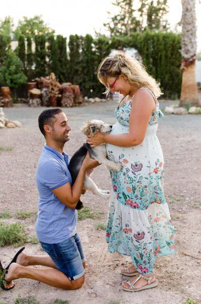 Fotografía de una pareja con su perro. La mujer está embarazada, de pie y de perfil. El hombre está arrodillado de perfil. En sus brazos tiene cogido a su perro, quien a su vez descansa su cabeza encima de la barriga de la mujer. La mujer está acariciando la cabeza del perro. Ambos miran a su perro con mucha ternura