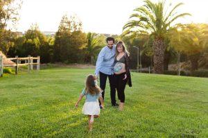 Fotografía de una pareja de pie, cogidos por la cintura. Ella está embarazada y tiene la barriga pintada por Colorehadas. Están mirando a una niña que corre hacia ellos con los brazos abiertos y descalza. Están en un campo verde con palmeras a lo lejos. Fotografía realizada en el Campus de Espinardo