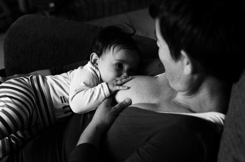 Fotografía en blanco y negro de una mujer amamantando a su bebé. La mujer está sentada sobre un sillón y encima de ella tiene a su bebé de unos 5 meses. A la derecha de la imagen está la mamá, pero no se le distingue la cara porque la foto está hecha desde encima de su hombro y su cara aparece de perfil. Sí se ve a la niña tomando pecho, con su mano derecha posada sobre el pecho de su mamá y mirándola con los ojos bien abiertos. La mamá tiene su mano izquierda colocada bajo la mano del bebé y su brazo derecho está bajo el cuerpo del bebé sujetándolo.