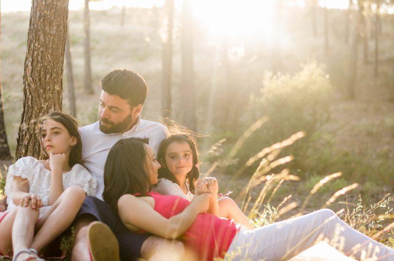 Fotografía de una familia compuesta por mamá, papá y dos niñas. El papá y las dos niñas están sentados, papá en el centro y las hijas a los lados. La mamá está delante recostada sobre las piernas y el pecho de papá. Se miran entre ellos. Están bañados por la luz del atardecer