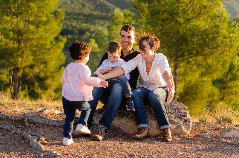 Fotografía a color de una familia compuesta por mamá, papá y dos niños. Papá y mamá están sentados sobre una roca. El niño está sentado sobre las piernas de su papá. La niña está un poco alejado de ellos y corre hacia su mamá, quien tiene los brazos abiertos para recibirla. Fotografía tomada al atardecer en el Valle de Murcia