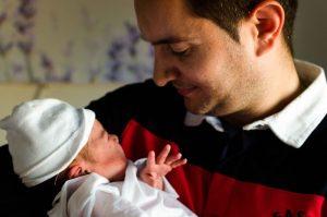 Fotografía a color de un papá con su bebé recién nacido. Imagen tomada en el hospital Virgen de la Arrixaca de Murcia. Del papá solo se le ve desde el pecho hasta la frente. El bebé está en brazos del papá. Ambos se miran