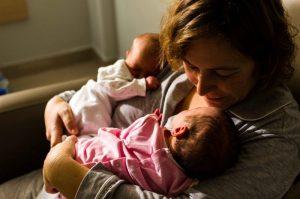 Fotografía a color de una mamá con sus dos bebés mellizos recién nacidos. Tiene cogidos a cada bebé con un brazo. Ambos están dormidos. Y mamá mira a uno de ellos, que lo tiene tan cerca de su cara que seguro que puede aspirar su aroma. Fotografía hecha en el hospital Quirón de Murcia
