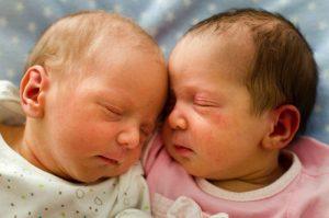 Fotografía a color de las caras de dos mellizos recién nacidos. Ambos están dormidos y están muy juntos, con las frentes pegadas.