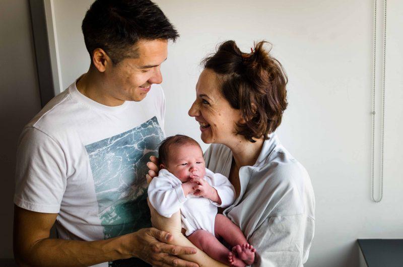 Fotografía hecha en el Hospital Virgen de la Arrixaca de Murcia. Aparecen mamá, papá y su bebé recién nacido. Mamá tiene al bebé en brazos semi sentado y mira muy sonriente a papá. Papá está cerca de ellos acariciando a ambos y mirando a mamá mientras se ríe también.