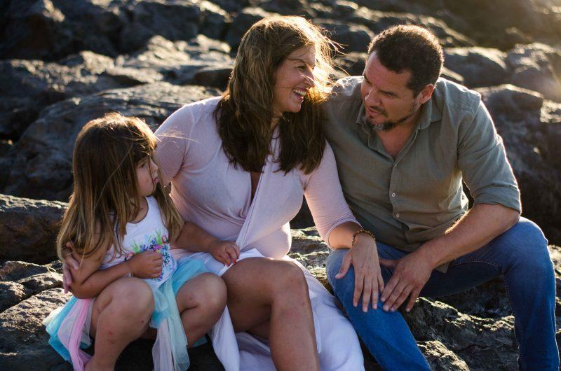 Fotografía de una familia compuesta por papá, mamá e hija. Están sentados en unas rocas al atardecer. Mamá está en el centro, apoyada ligeramente sobre papá y pasándole el brazo a su hija por detrás mientras sonríe a papá. Y papá e hija se miran