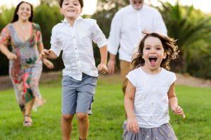 Imagen de una familia corriendo en una zona verde de Murcia al atardecer. En primer plano está la niña, con cara de velocidad y exultante de felicidad. Por detrás aparecen su hermano, papá y mamá corriendo para intentar ganarla, pero están más atrás y desenfocados.