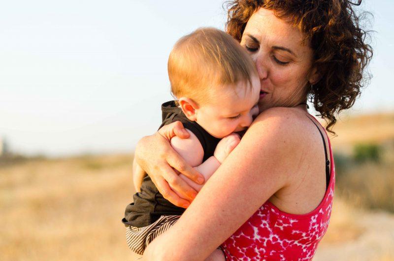 Fotografía de una mamá con su bebé de más o menos 1 año. Lo tiene en brazos, bien cogido. El brazo izquierdo lo pasa por debajo de su culete y con el derecho le atrae hacia sí. El bebé está arrebujado hacia ella y con su nariz cerca del hombro. Mamá está mirando hacia su bebé y, de tan pegada que está a su cara, la nariz la tiene algo arrugada.