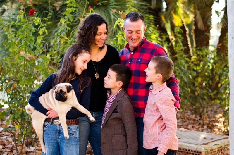 Fotografía de una familia compuesta por mamá, papá, una hija, dos hijos y un perro. Es una fotografía hecha al atardecer con un fondo de plantas verdes. Mamá y papá están en la parte de detrás mirando a sus hijos. La niña está a la izquierda de la imagen delante de su mamá y con el perro en brazos. Y los dos niños están también delante de mamá y papá. El niño que está en medio mira a su hermana, quien también le mira a él. Y el niño que está a la derecha mira hacia su mamá.
