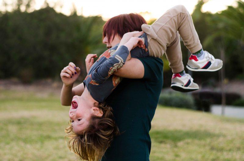 Imagen de una mamá cogiendo a su hijo por encima de su hombro. Pero el niño está boca arriba encima de ella y riéndose a carcajadas. Se le ve el cuerpo entero, mientras que a su madre, que está de perfil, no se le ve prácticamente nada, solo el lateral del cuerpo y la parte superior de la cabeza, porque está tapada por su hijo. Ella está fotografiada de cintura hacia arriba. Están en un entorno verde, con árboles detrás en Murcia.