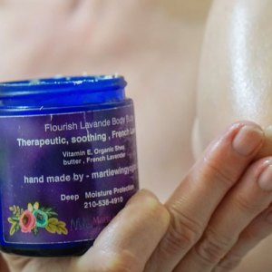 Woman moisturizing her elbow with lavender shea butter