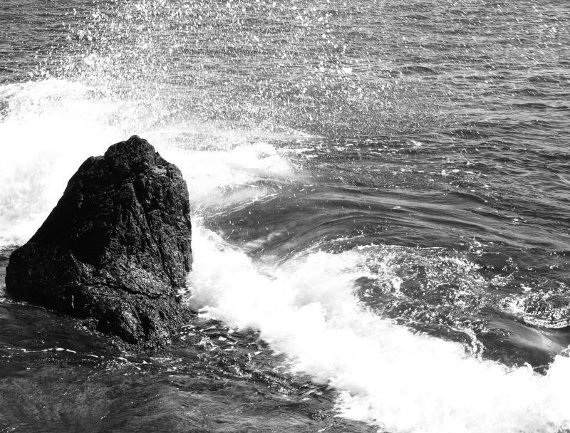 Eine Welle bricht sich an felsiger Küste in Newport, Rhode Island