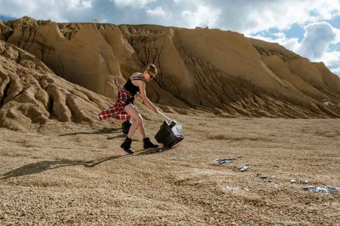 woman in red and white dress sitting on brown sand