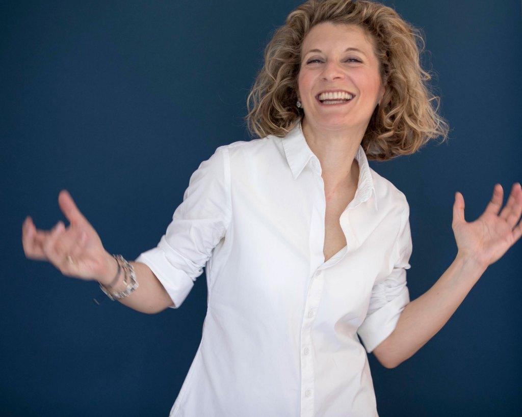 Martina Töpfer lächelt und gestikuliert mit den Armen