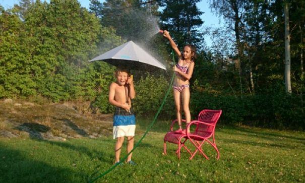 Lek med vattenslang och paraply