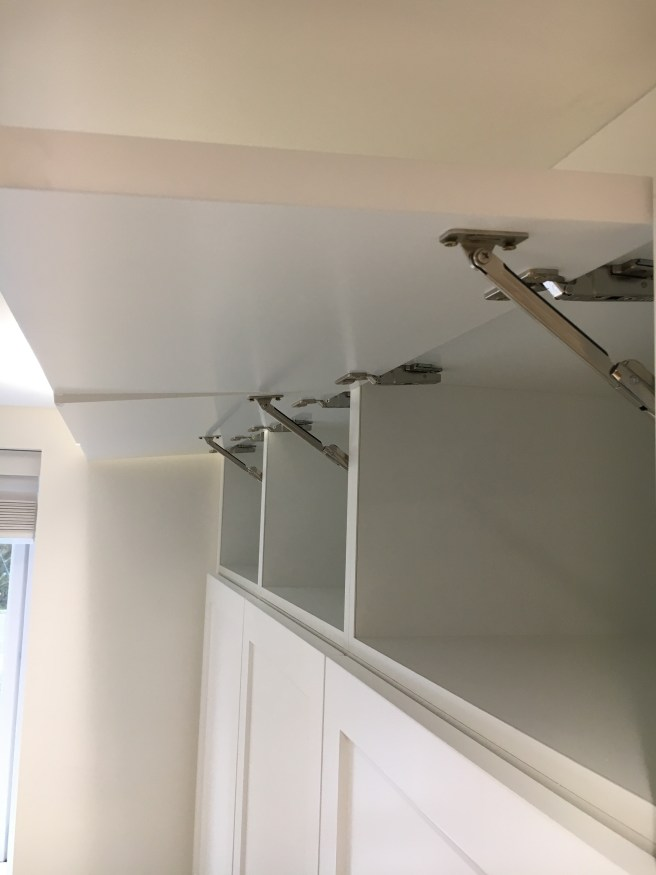 Soft close mechanism for top boxes of floor to ceiling wardrobes