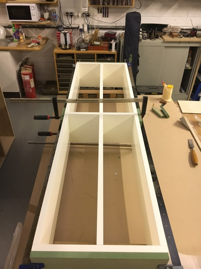 Spray finished bedroom storage box being glued up ready to be fitted on site