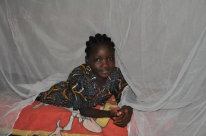 Samiratou under her mosquito net over her bed