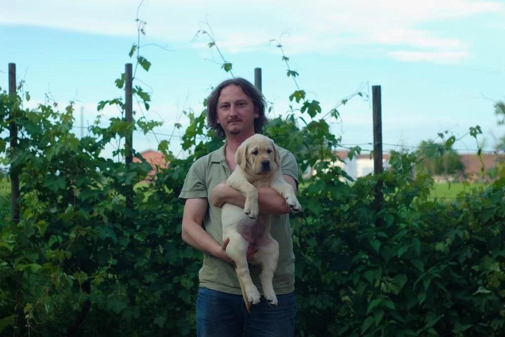 allevatore e cucciolo labrador biondo