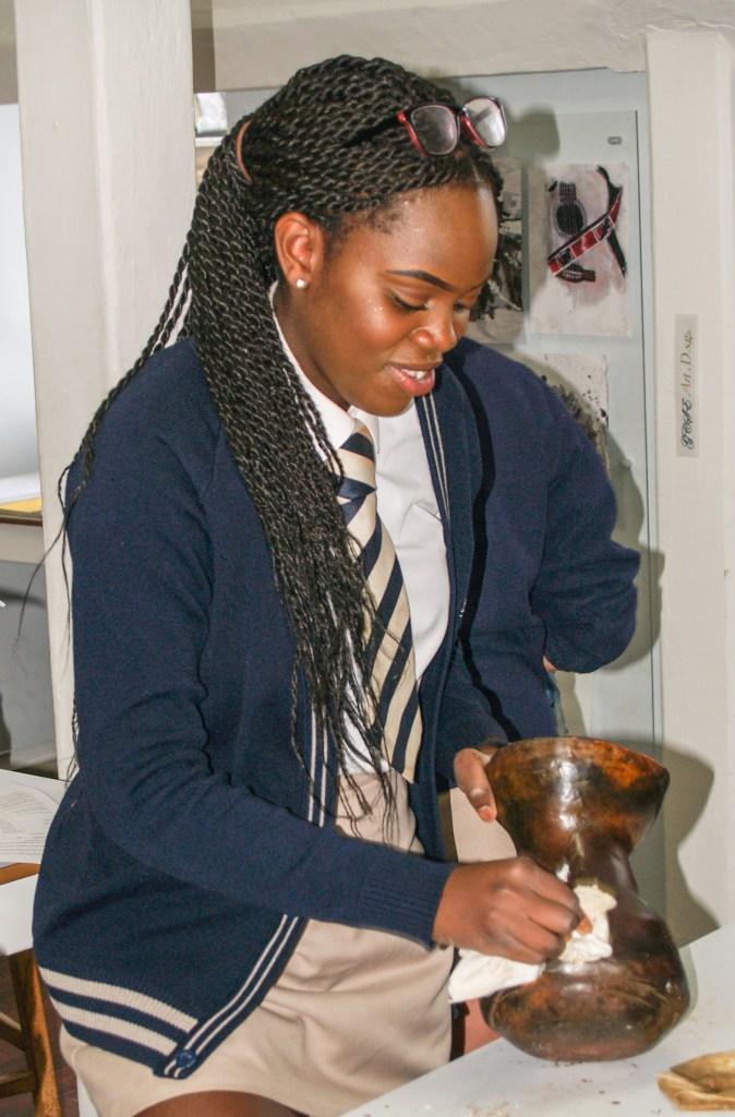 Student polishing her pot