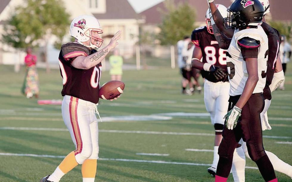 Mike Dempsey, left, gets a high five after running for a ceremonial touchdown during a Fargo Invaders football game on Saturday at Fargo Shanley's Sid Cichy Stadium.  Michael Vosburg / Forum Photo Editor