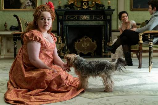 Nicola Coughlan as Penelope Featherington in Netflix's Bridgerton playing with a puppy.