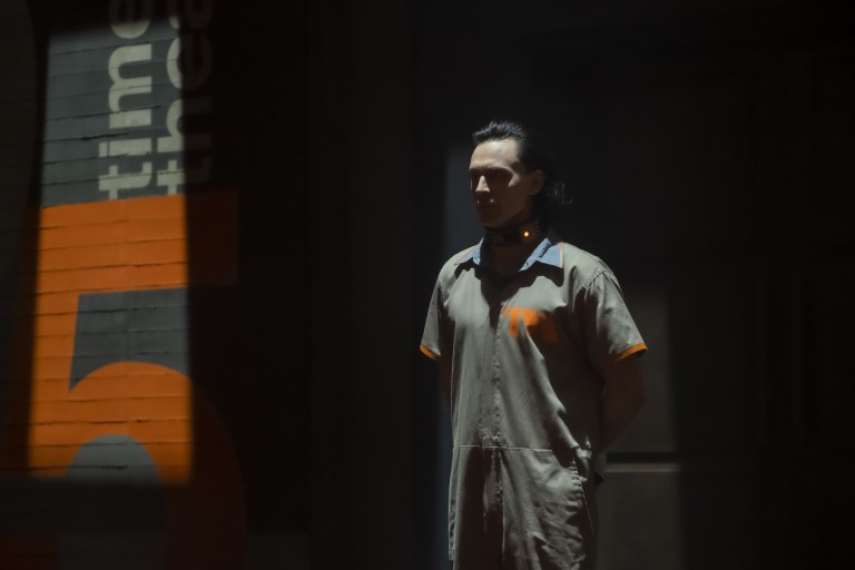 """Tom Hiddleston as Loki stands before questioning in Loki's episode one titled """"Glorious Purpose"""" on Disney Plus."""