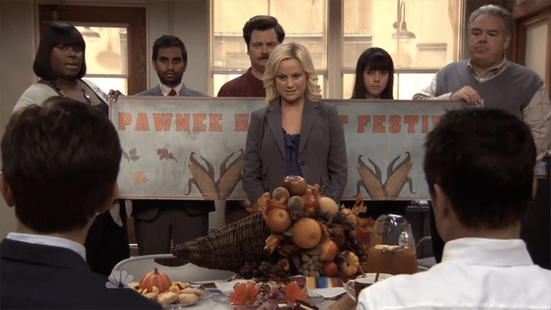 Screenshot from Parks and Recreation's season three episode one, showcasing autumn vibes with Harvesst Festival poster