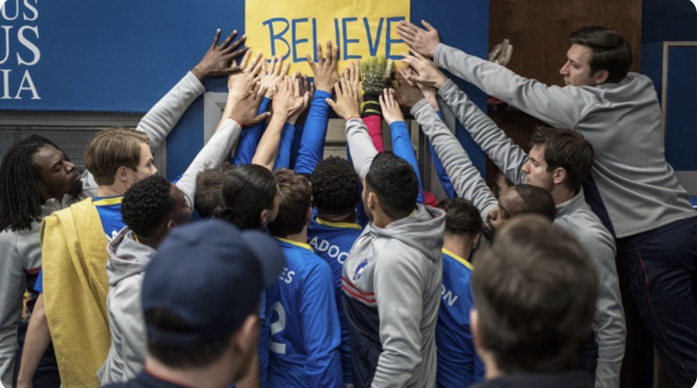 """The team touches the """"believe"""" sign in Ted Lasso's """"Inverting the Pyramid of Success"""""""