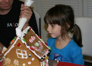 preschooler decorates gingerbread house