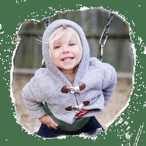 preschool girl smiling and swinging on swings on her belly.