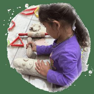 preschool girl working with play dough