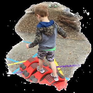 preschool boy walks across bridge he has built out of toys