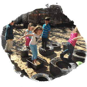 preschool and kindergarten children jump across the sandbox on tires