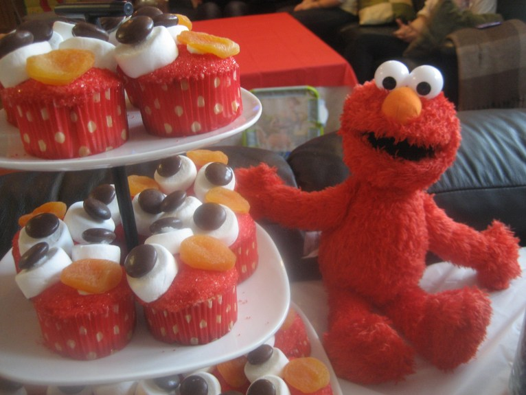 Elmo doll sitting next to a three tiered cake stand with Elmo themed cupcakes
