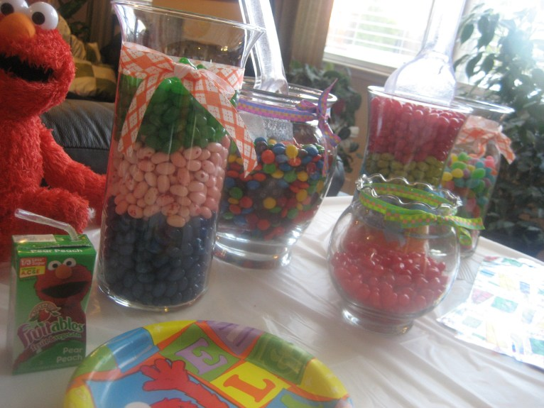 Colorful candy displayed in candy jars with scoopers