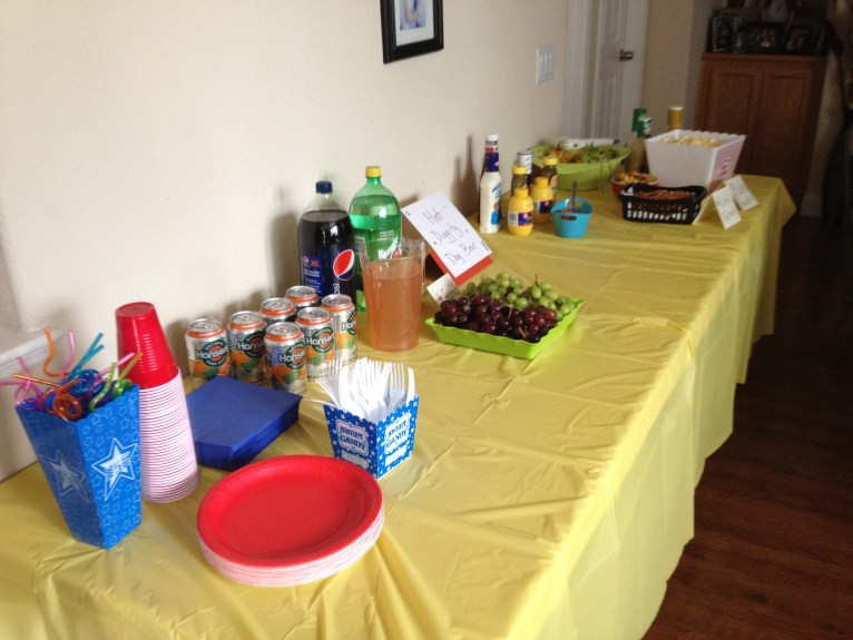 Long table with yellow table cloth. Topped with food, plate, cups, soda and juice.