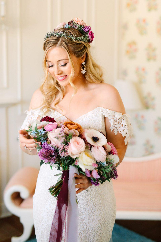 Bride admiring bouquet - www.marycostaweddings.com