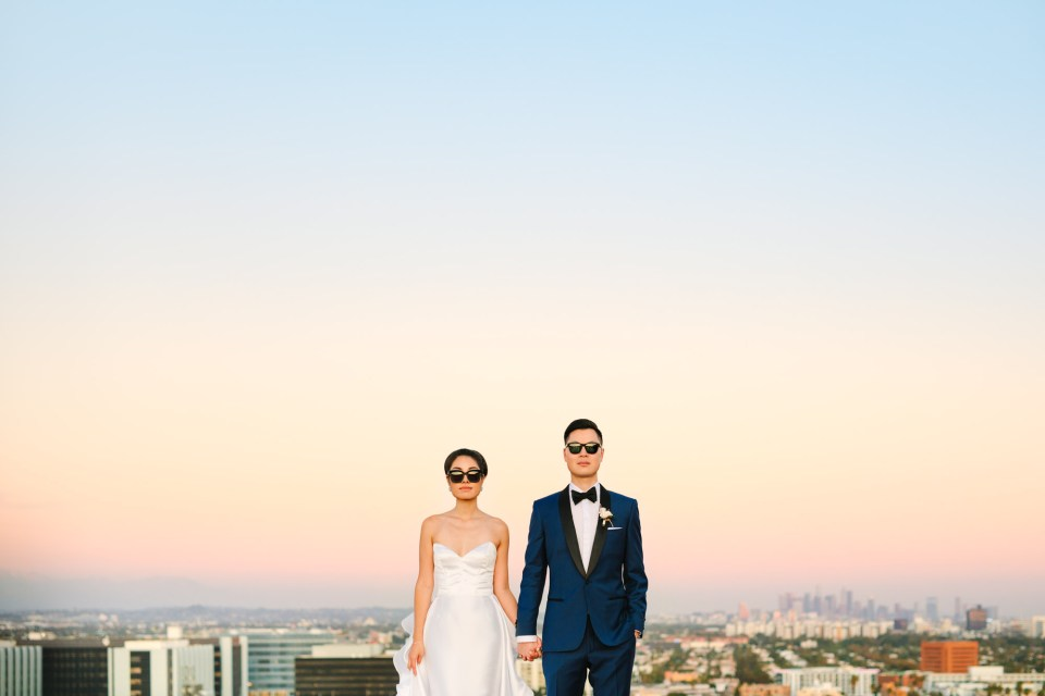 Bride and groom in sunglasses with Los Angeles skyline Indian Fusion wedding at Fig House Los Angeles by Mary Costa Photography