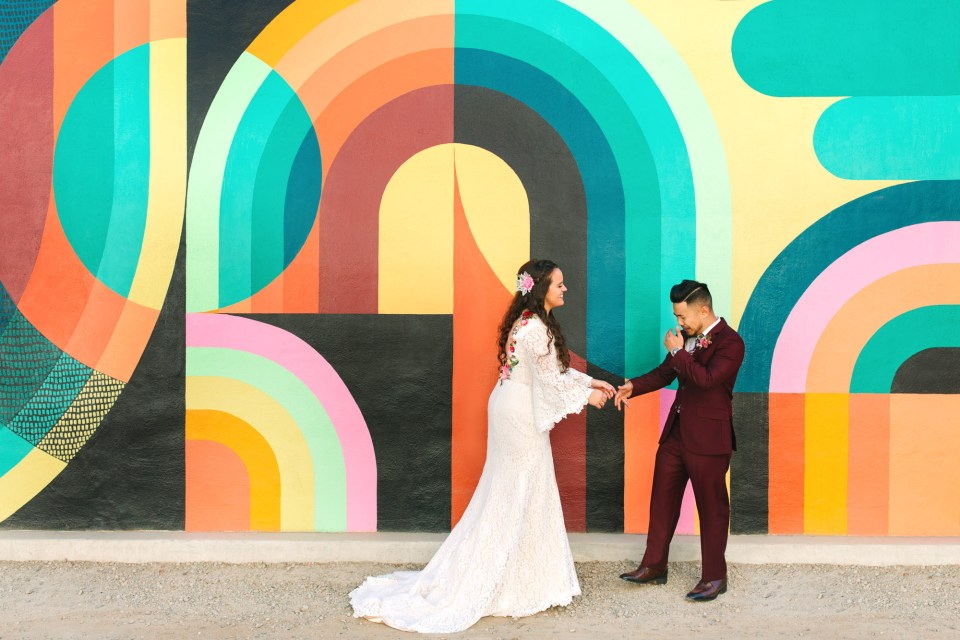 Bride and groom first look in front of colorful Sacramento mural by Mary Costa Photography