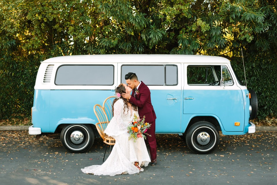 Bride and groom kissing with VW Van by Mary Costa Photography