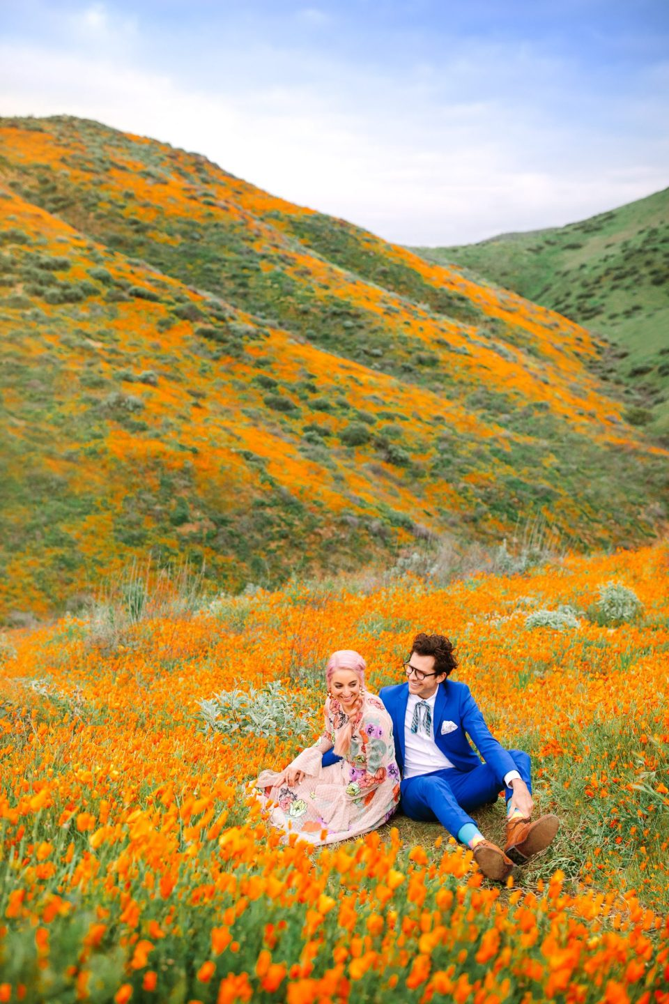 Couple in poppy field by Mary Costa Photography