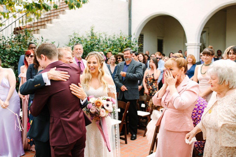 Groom and father of the bride embracing during ceremony by Mary Costa Photography