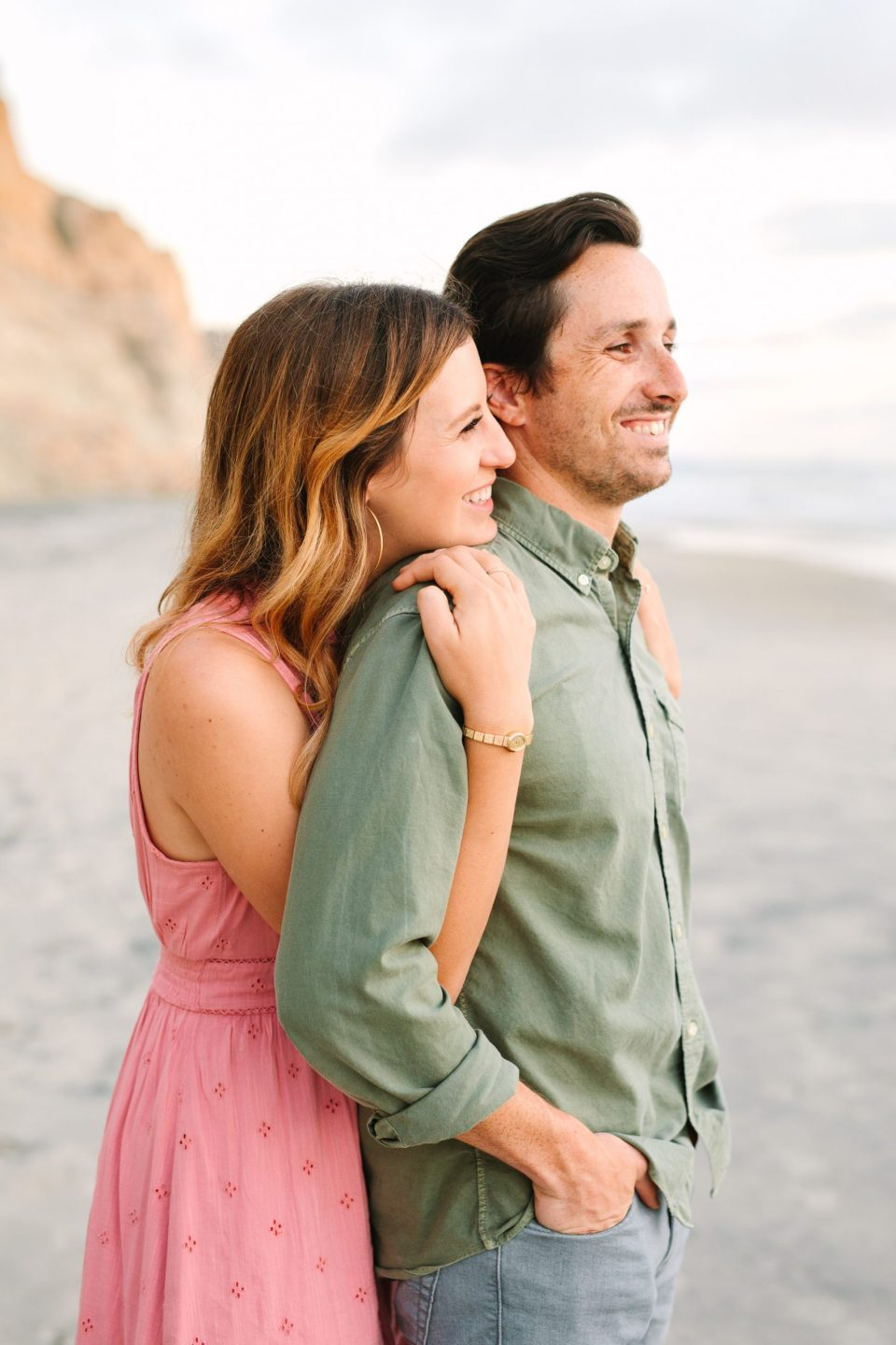 Couple embracing at Torrey Pines Beach by Mary Costa Photography