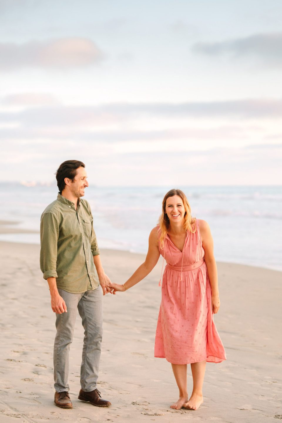 Couple laughing on beach for engagement session by Mary Costa Photography