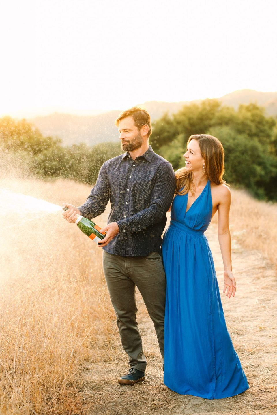 Couple popping champagne by Mary Costa Photography