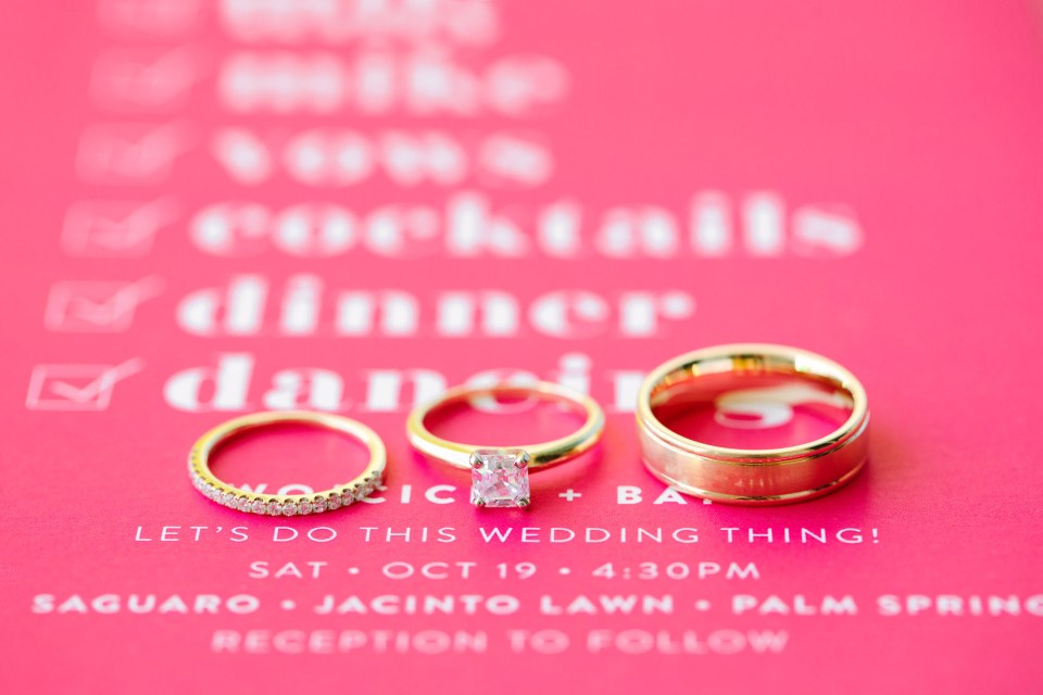 Wedding rings on pink invitation www.marycostaweddings.com