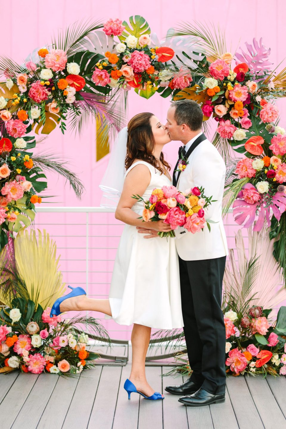 Couple kissing at colorful wedding ceremony arch www.marycostaweddings.com