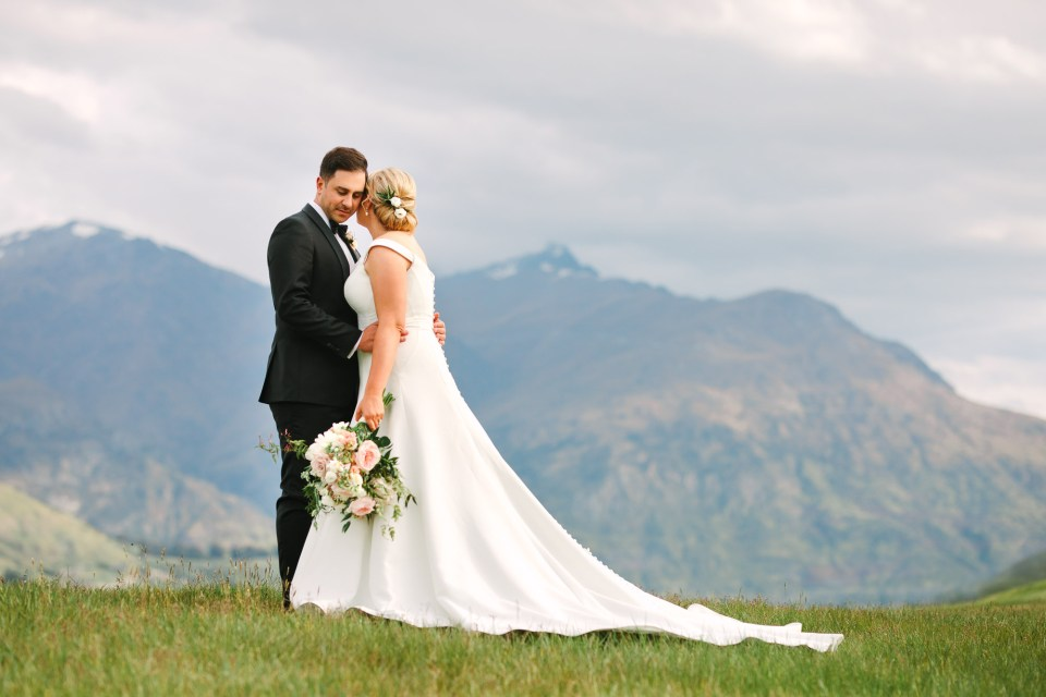 Couple embracing by mountain at Millbrook Resort New Zealand Indian Fusion wedding at Fig House Los Angeles by Mary Costa Photography